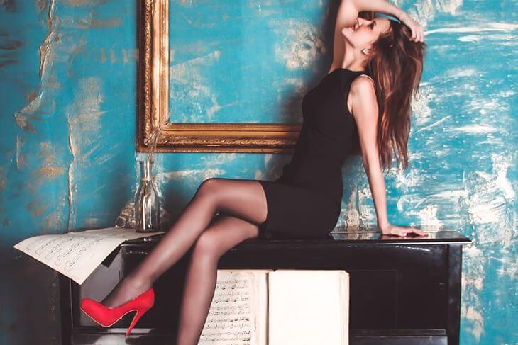 Devojka nosi crnu usku haljinu uz crvene štikle