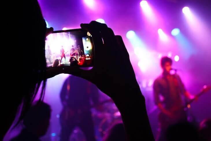 Devojka fotografiše nastup benda u klubu