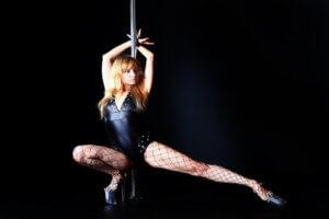 Devojka igra oko šipke i izvodi striptiz
