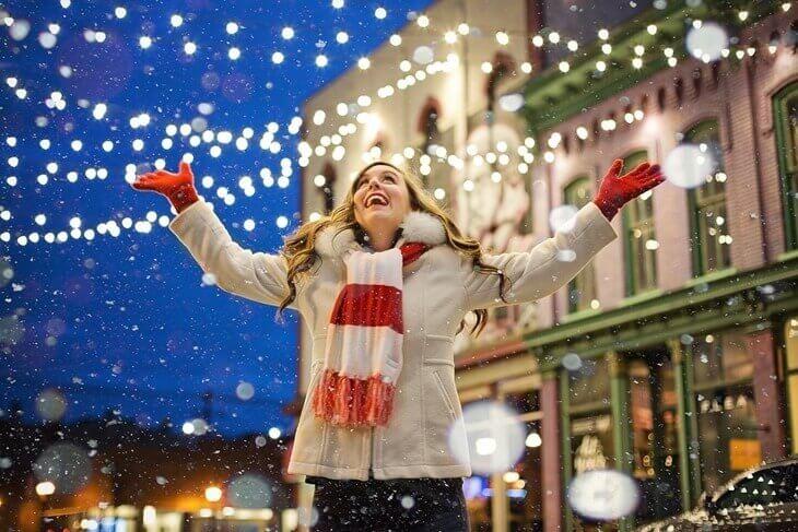 Srećna devojka ispod novogodišnje rasvete