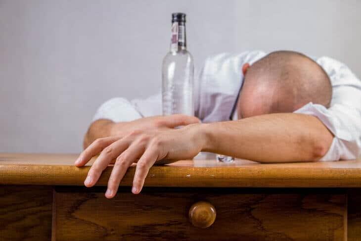 Čovek koji leži za stolom sa flašom alkohola