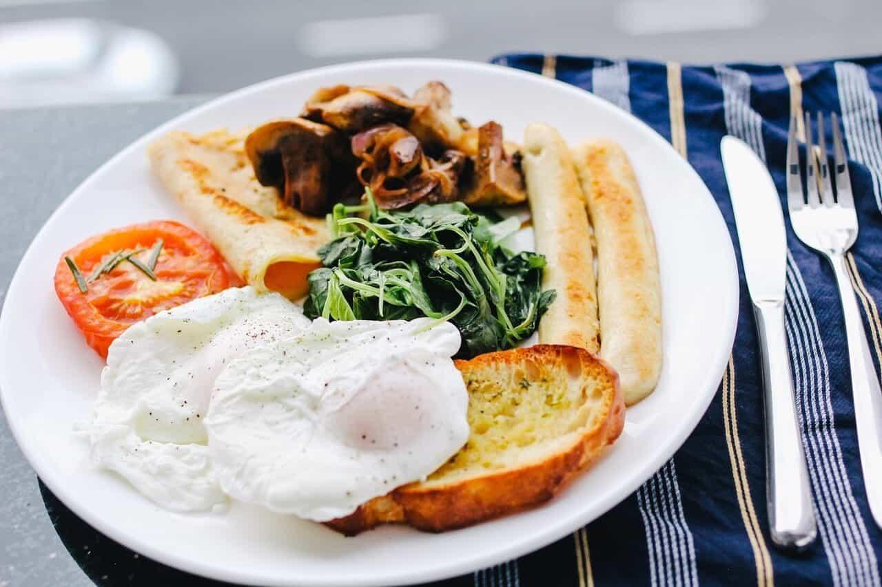 Spremljen doručak u belom tanjiru pored koga se nalaze viljuške