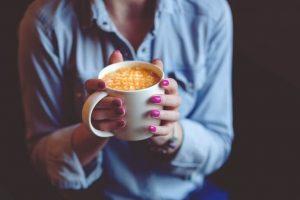 Devojka koja drži kafu u rukama