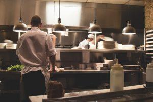 Kuvar u kuhinji restorana priprema jelo