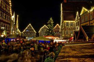 Božićni market na trgu koji je okružen osvetljenim kućama