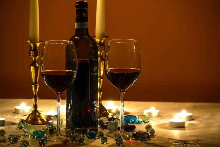 Dve čaše i flaša crvenog vina na stolu sa svećama