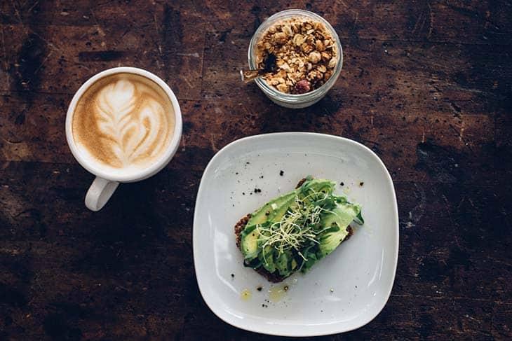 Šolja kafe, posuda i sendvič na stolu iz ptičije perspektive
