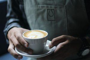 Konobar sa obe ruke drži šolju kafe