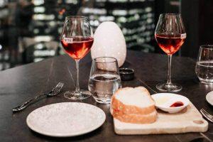 Dve čaše vina i hleb pored tanjira na stolu