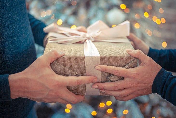 Darivanje poklona upakovanog u ukrasni papir sa roze mašnom