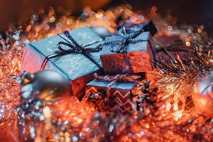 Poklon za novu godinu upakovan u ukrasni crni papir