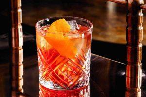 Kristalna čaša u kojoj je negroni piće sa ledom i korom pomorandže